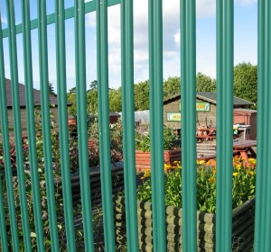 Strong metal fencing protecting an urban allotment site.