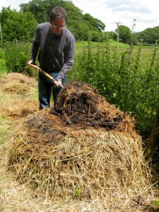 Turning a 'hot' garden compost heap built from 'greens' and 'browns' to allow in more air and keep temperatures high.