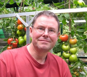 John Walker, earth-friendly gardening and environment writer and author in his lean-to greenhouse powered by renewable modern sunshine.